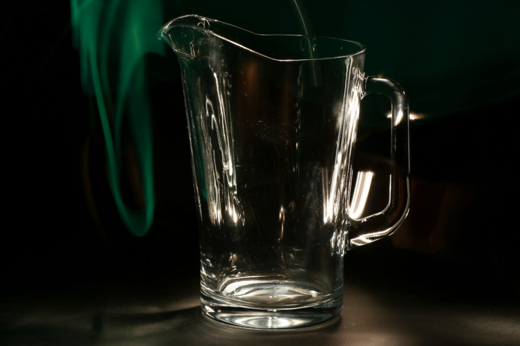A still life of a glass jug against a black background, lit with torches